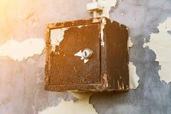 老电盾在房子,垂悬在墙壁上的一个生锈的金属箱子的剥落的墙壁上垂悬 免版税库存图片