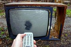 老电视和遥控在街道上的手上 免版税库存图片