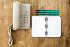 老电话、空白的笔记本和三支铅笔 免版税库存图片