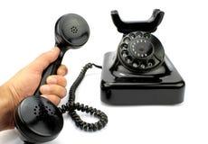 老电话和收货人在手中 免版税图库摄影