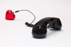 老电话接收器和绳子连接与红色心脏 图库摄影