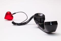 老电话接收器和绳子连接与红色心脏 库存图片