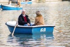 老男人和妇女一条小船的在Retiro在马德里停放池塘 库存图片