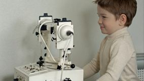 老男性医生通过被切开的灯审查男孩的眼睛 免版税库存图片