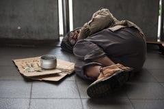 老病的叫化子或无家可归的肮脏的人睡眠在小径与捐赠碗,美金,硬币,纸纸板与帮助文本 图库摄影