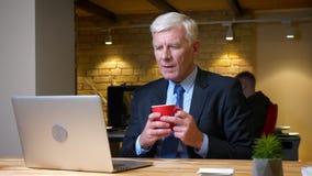老白种人办公室工作者特写镜头射击使用膝上型计算机和饮用的咖啡的户内在工作场所的办公室 股票录像