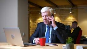 老白种人商人特写镜头射击谈话在电话,当使用膝上型计算机户内在的时办公室 股票录像
