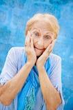 惊奇的资深妇女画象用在面孔的手在蓝色ba 图库摄影