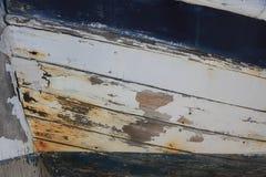 老白色和蓝色木小船 库存照片