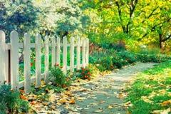 老白色木篱芭在树、花和Bu中的一个公园 库存照片