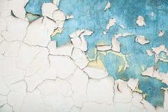 老白色破裂的油漆纹理在蓝色墙壁上的 库存图片