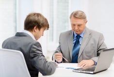 更老的人和年轻人开会议在办公室 库存图片