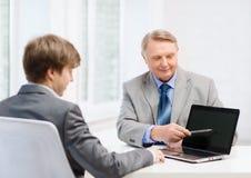 更老的人和年轻人有便携式计算机的 库存图片