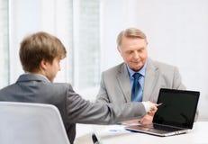 更老的人和年轻人有便携式计算机的 图库摄影