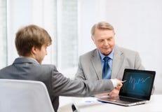 更老的人和年轻人有便携式计算机的 免版税图库摄影