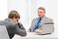 更老的人和年轻人有论据在办公室 免版税库存照片