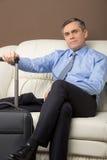 更老的人坐有行李的长沙发 免版税库存图片