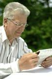 更老的人读书报纸 库存图片