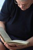 更老的人读在他的膝部的一本书 图库摄影