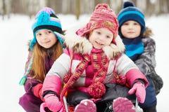 更老的女孩和男孩推挤女孩坐的雪撬 免版税库存照片