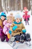 更老的女孩推挤有两个小孩的雪撬 免版税库存照片
