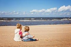 更老的姐妹和弟弟在毛线衣坐beac 免版税库存图片
