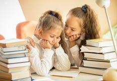 更老的姐妹安慰性更加年轻一个,当做家庭作业时 免版税库存照片