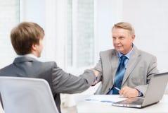 更老的握手的人和年轻人在办公室 库存图片