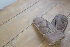 老皮革手套和围巾在木桌上 免版税图库摄影