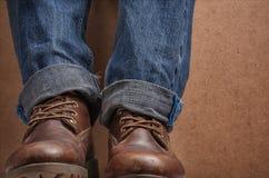 老皮革棕色靴子和蓝色牛仔裤 免版税库存照片