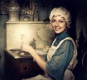 老盖帽的妇女有烛台的 库存图片