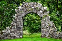老石入口墙壁在绿色庭院里 库存照片