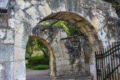 老石墙和拱道有树的和藤和垂悬灯笼和一个错误铁门 图库摄影