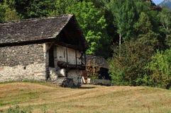 老石房子和草甸在意大利阿尔卑斯 图库摄影