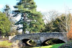 老石桥梁和树反射在河 免版税库存图片