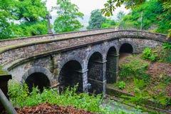 老石桥梁在庭院里 免版税库存照片