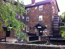 老石头有水轮的被围住的旅馆 库存照片