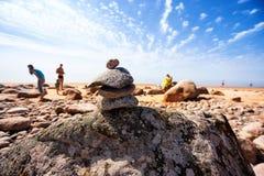 老石头的金字塔在海滩的与太阳度假者 库存图片
