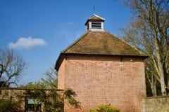 老砖与赤土陶器瓦屋顶的被修造的鸠棚反对天空蔚蓝-图象 免版税库存照片