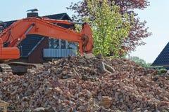 老砖堆和水力推土机挖掘机在背景中武装 库存照片