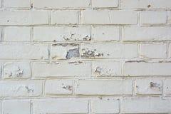 老砖墙表面上的白色破裂的绘画 免版税库存照片