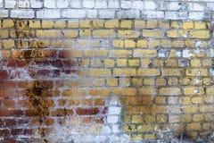 老砖墙,被风化的脏的纹理,黄色和白色油漆与铁锈弄脏 图库摄影