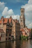 老砖瓦房和钟楼在运河` s在一个晴天渐近在布鲁日 库存照片