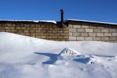 老砖瓦房和雪堆 图库摄影