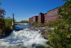 老砖磨房大厦,瀑布,河,在明亮的晴天 免版税库存照片