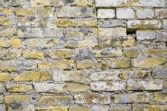 老砖击毁了与孔、侵蚀和破坏的墙壁米黄难看的东西表面被风化的具体水泥 纹理,背景 免版税库存照片