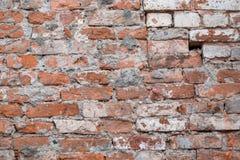 老砖击毁了与孔、侵蚀和破坏的墙壁biege难看的东西表面被风化的具体水泥 纹理,背景 免版税库存照片