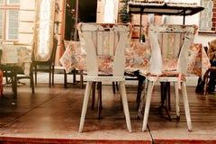 老破旧的减速火箭的椅子和五颜六色的桌在咖啡馆大阳台在EU 免版税库存照片