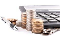 老硬币、计算器和铅笔的专栏 免版税库存图片