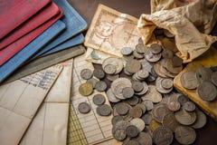 老硬币和银行存折在难看的东西背景。 免版税图库摄影